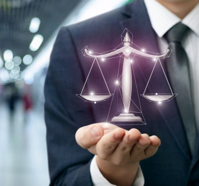 Lawyer shows the scales of justice in hand on a blurred background.